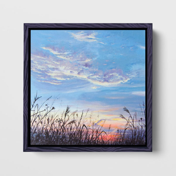 framed painting of a meadow and the sky hanging on a wall