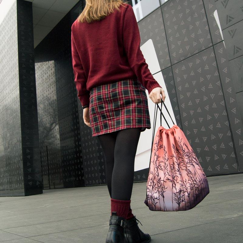 woman carrying an orange drawstring bag