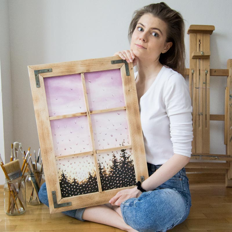 girl holding a painting framed in a window frame