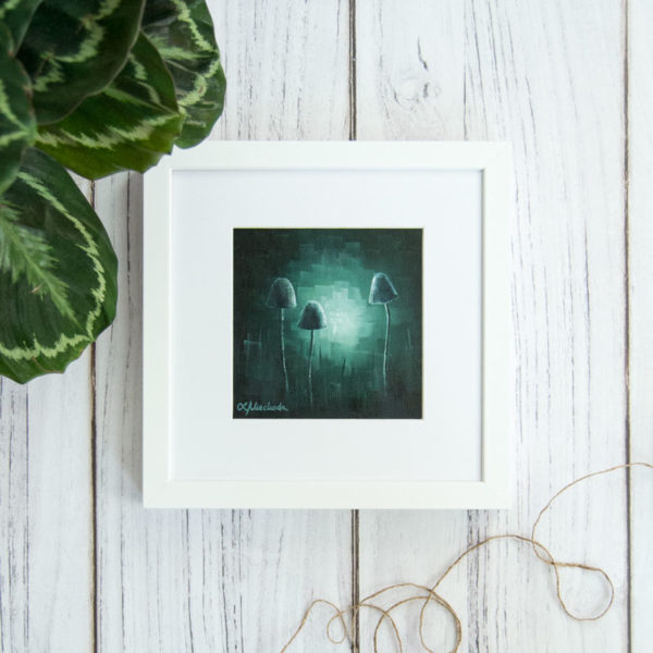 framed painting of moonlit fungi laying on the wooden floor