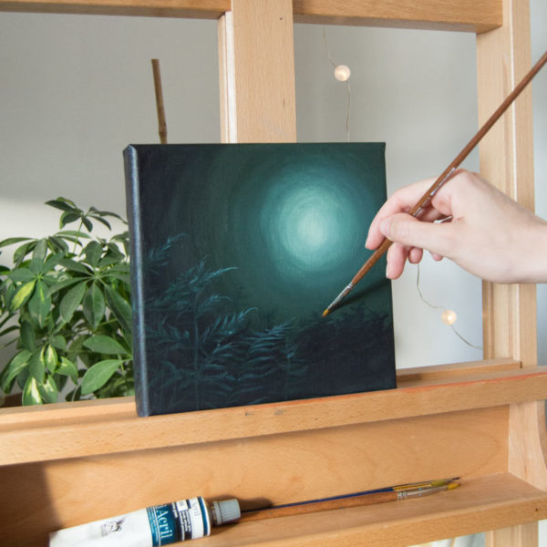 hand painting a green painting on an easel