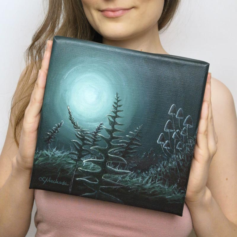 woman holding a green painting of ferns and fungi in the moonlight