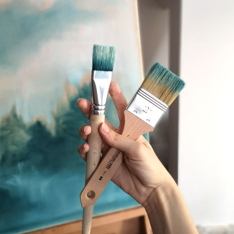 hand holding brushes in front of a painted canvas